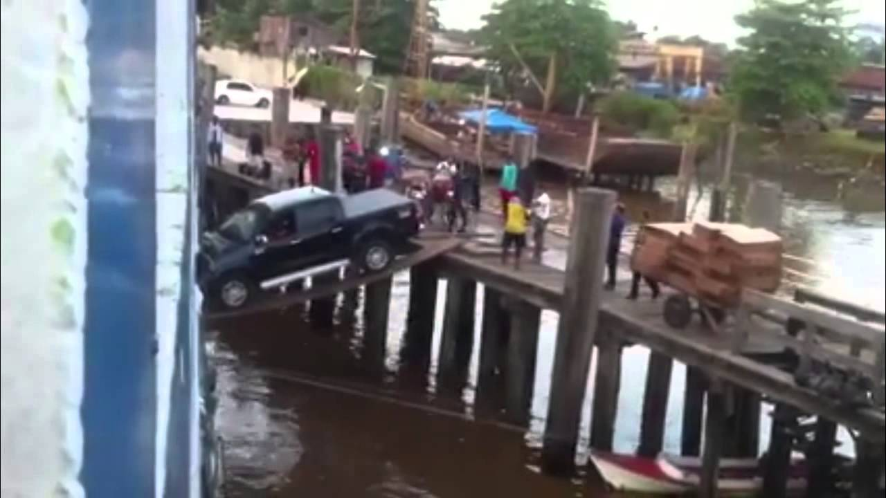 Car attempting to load on a ship over some planks