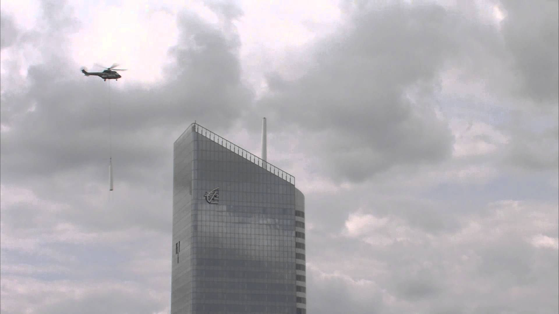 Precision helicopter flying installing a building spire